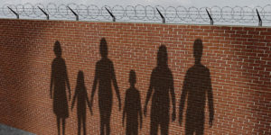 Shadows of a family cast against a brick wall with barbed wire